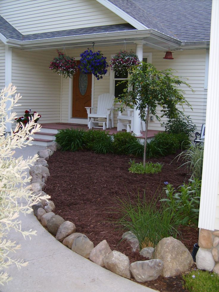 Use rocks as a natural edging or border to your walkway.  It also doubles as a barrier from your woodchips blowing onto the sidewalk.