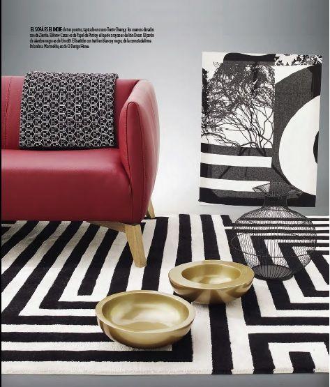 El sofá es el Indie de tres puestos, tapizado en cuero Trento Cherry, y los cuencos dorados son de Zientte. El throw Casas es de Papel de Punto y el tapete a rayas es de Irán Decor. El jarrón de alambre negro es de Unodöt. El bastidor con textil en blanco y negro, de la connotada firma finlandesa Marimekko, es de Q Design Home.