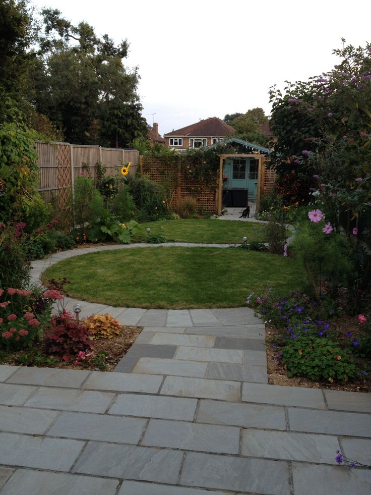 curved s shaped path between two circular lawns enhances the sense of space in a long narrow back garden