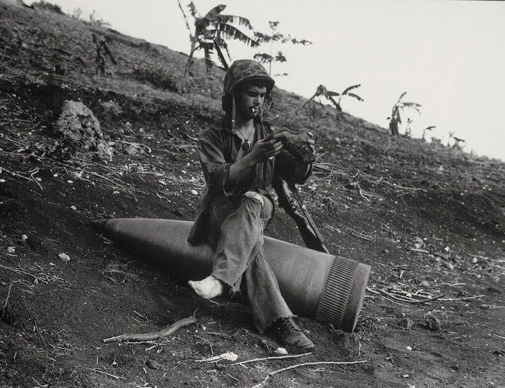 US Marine emptying sand from his boot and having a smoke on an unexploded 16-inch shell fired from a battleship in support of the Battle of Saipan, 1944