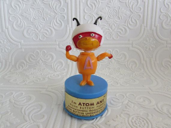 A 1960s vintage Im Atom Ant Push Button Puppet is next. This very cool little push button puppet is in terrific condition considering age and the procedure to play with this item. Little Atom Ant with his White helmet, Red mask, Orange Suit, Red Gloves and Black tenticles is too cute. Measuring: 3 1/2 tall, clearly marked on the bottom: Kohner Bros. Inc., East Patterson, N.J., Hanna Barbera Productions, Inc. Made in Hong Kong. Front Gold sticker still attached with instructions on how to...