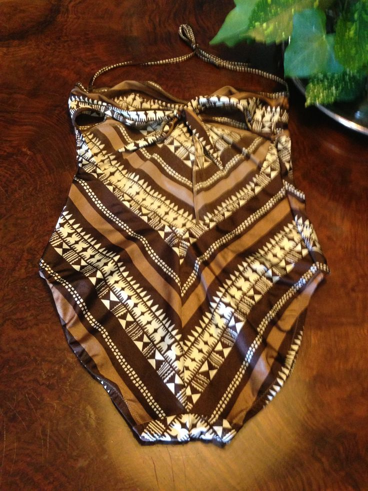(back) definitely 70s for this super elegant swimsuit, variety of brown and drawings embellished with a wood and leather brooch