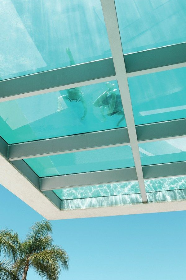 The underside of the cantilevered pool structure is glazed, allowing sunlight to filter through the water to the entry ramp and adjacent ter...