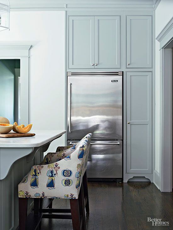 Tucking a refrigerator into cabinetry gives the large appliance a built-in look. Custom cabinetry also lets you create special storage areas. The tall cabinet in this cottage kitchen has a drawer at the bottom for children's dishware, allowing them to be part of the table-setting routine./