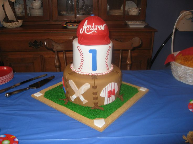 "Baseball 1st Birthday - Made this for a friend's son's first birthday.  The baseball cap topper is RKT covered in fondant.  6"" tier made to look like a baseball with red RI stitching.  9"" tier is inspired by a baseball glove - each panel is ""laced"" together with ""leather"" laces and ties on the cake board.  Each panel has a baseball themed picture.  Cakeboard  is a baseball diamond covered with RI grass and graham cracker crumbs for dirt around the bases.  TFL!"