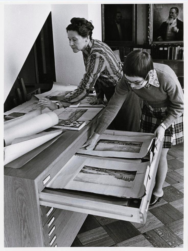 SKS:n juhlasalissa kirjaston kokoelmia järjestämässä Kaija Virtanen (vas.) ja Marja Kukkonen Kuva: 1973, Timo Hämäläinen (SKS, kirjallisuusarkisto).