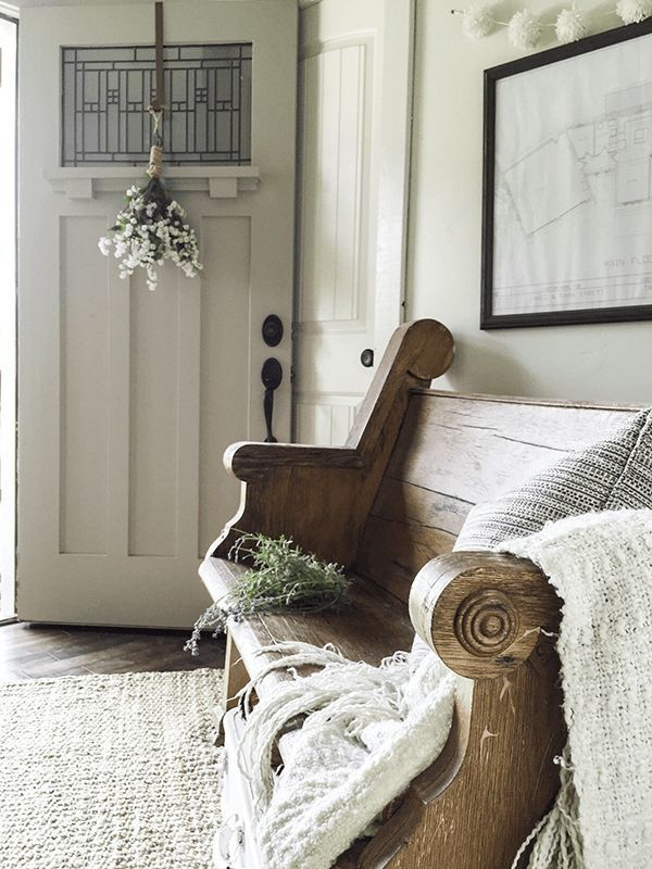 Beautiful farmhouse entry with an old pew, pompom garland and an antique front door!
