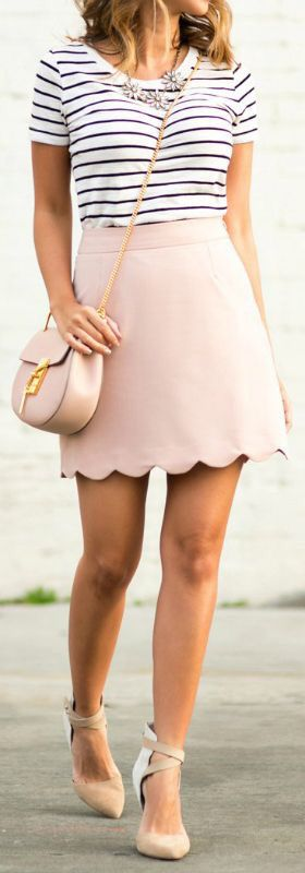 Blush skirt with a decorative hemline and a blue and white striped shirt tucked into it