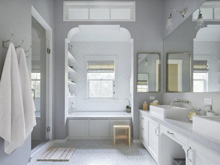 Bathroom: Transitional Master Bath In Contemporary Farmhouse. frameless shower door. glass door. white large bathroom. white vanity top. white vanity storage. wall mirror. alcove storage. wooden bathroom stool. wooden bathroom mat. metal towel hooks.
