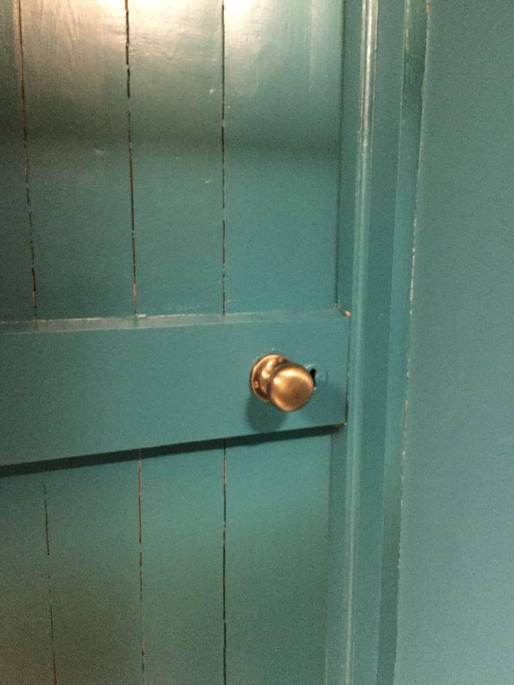 Antique brass door knob on plank door (painted in Farrow & Ball Vardo).