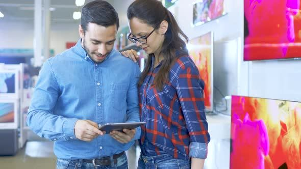 Young Beautiful Couple In the Electronics Store Looks at Latest Tablet Computer Models
