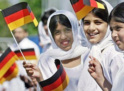 Muzułmańskie dziewczynki machają niemieckimi flagami podczas dorocznej muzułmańskiej kongregacji, po raz 11. zorganizowanej w Mannheim; fot. PAP