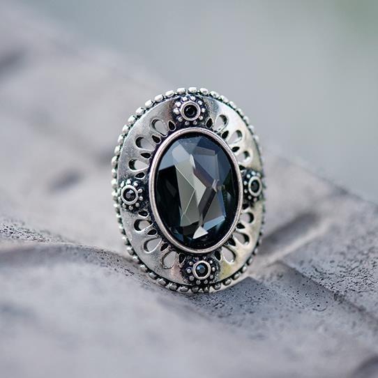 """De ovale vorm van het medaillon sluit prachtig om de vinger. Het """"kantwerk"""" in het medaillon komt goed tot zijn recht in de antieke verzilverde finish van de ring, maar de echte aandacht wordt getrokken door de hand gekloofde en gepolijste petrolkleurige steen. Een sieraad voor iedere vinger."""