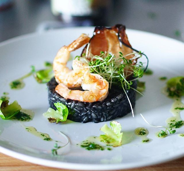 Homemade squid ink risotto, with pan seared shrimps, leaves of ...