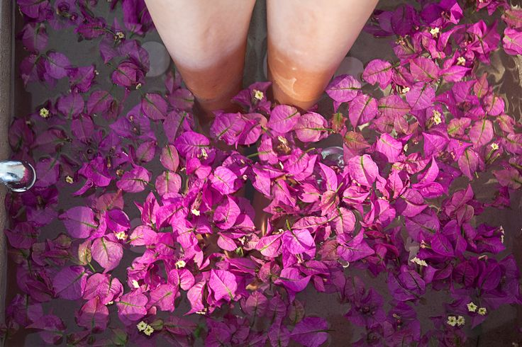 woman spa pedicure foot treatment with natural springwater and flowers