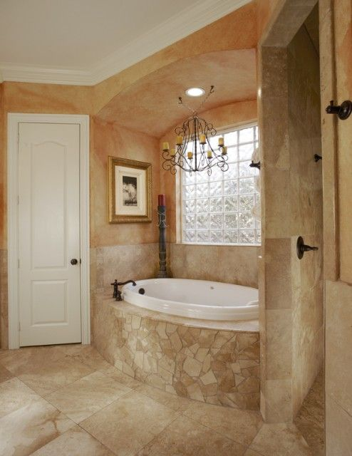 A Tuscan Style Master Bath With Worn Faux Finished Walls, Travertine  Wainscot And Roman