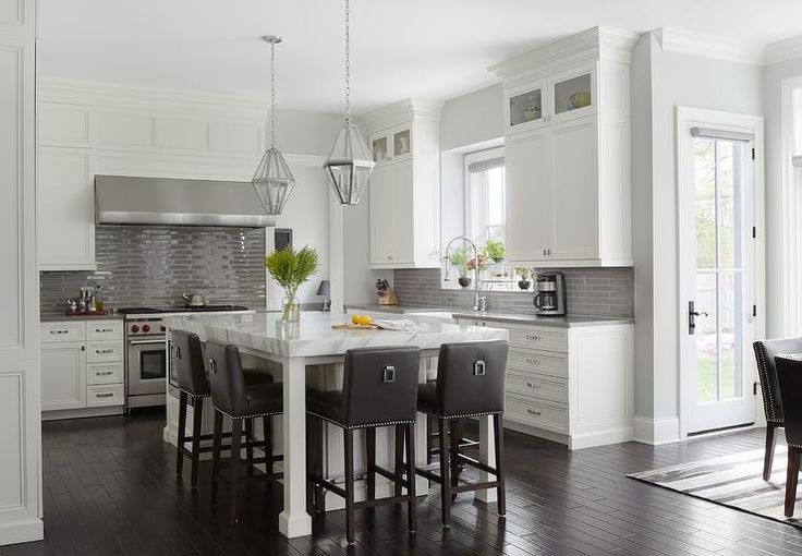 White and gray kitchen features white shaker cabinets paired with gray quartz countertops and a glossy gray linear tile backsplash.