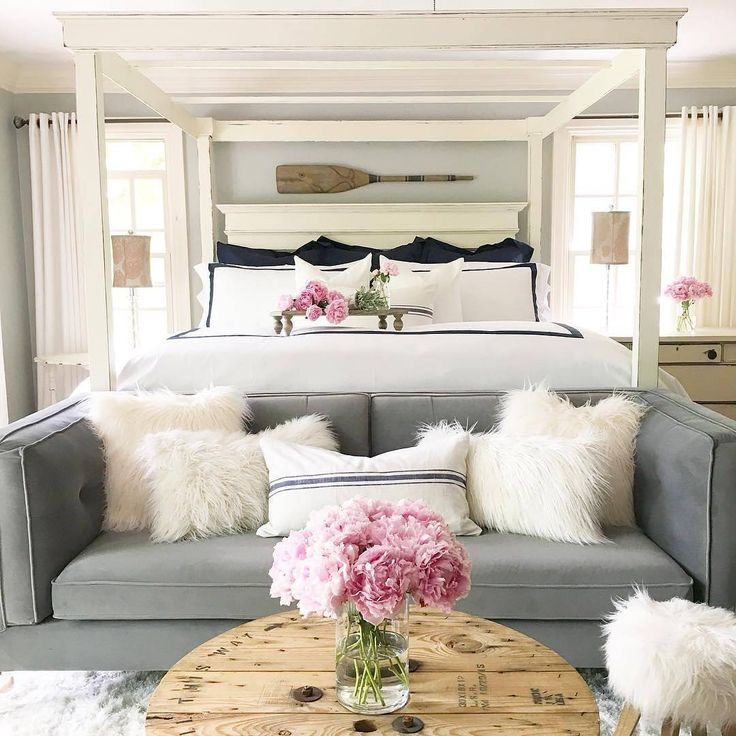 White and navy bedroom with grey sofa