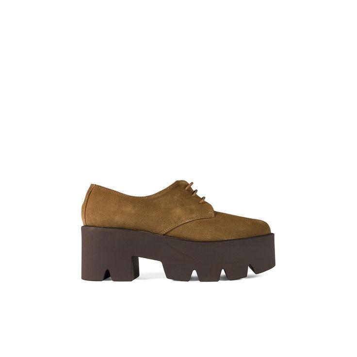 Zapato de mujer tipo Oxford realizado en ante, cierre de cordones con ojales ciegos. Suela de goma dentada y tacón ancho para aportar mayor comodidad.