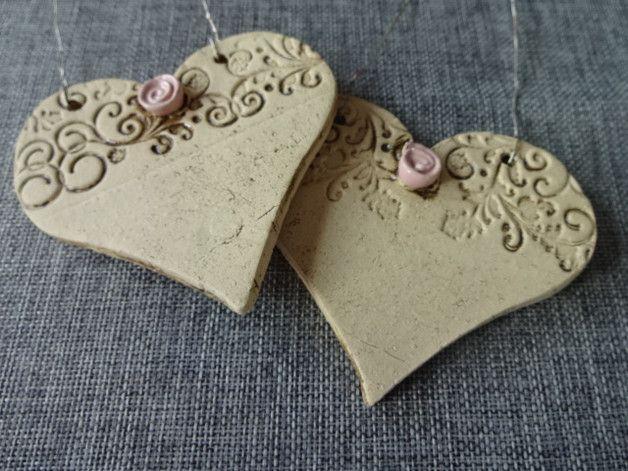 Die Keramikherzen wurden handtgetöpfert, das Röschen in Rosa glasiert und gebrannt. Das Herz ist ca. 9 cm breit und ca. 7 cm hoch.