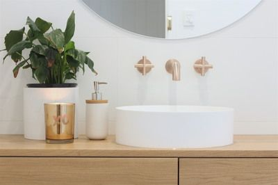 Brisbane Builder eclat building co. bathroom renovation. This light, modern and natural, bathroom features timber vanity, grey concrete floor tiles, marble tile feature wall, copper / rose gold astra walker tapware and freestanding bath