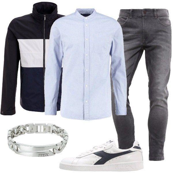 Look maschile casual, composto da una giacca nera blu e bianca con colletto alla coreana abbinato ad una camicia slim fit celeste chiaro e ad un paio di jeans grigi a sigaretta, sneakers basse bianche e un bracciale a catena in acciaio.