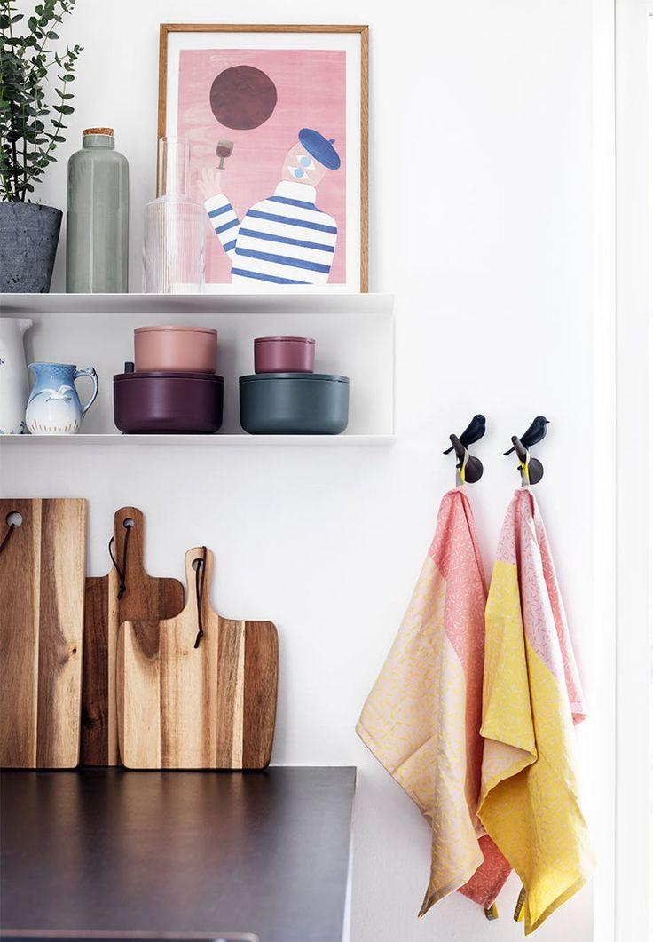 Nærbillede af detaljer i køkkenet med skærebrætter i træ og krukker, viskestykker og billede i feminine farver