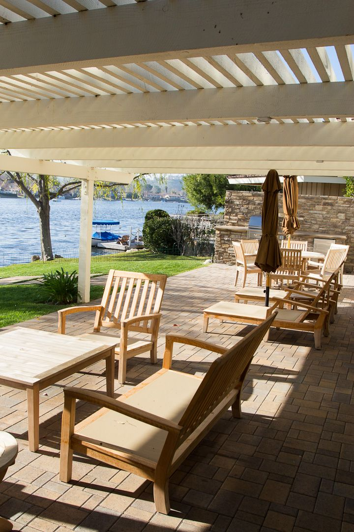 White wooden pergola covers a brick paved floor. The patio offers a great view of the lake. What kind of lake house do you want? #patiodecor #patiodesign #patioideas #patio