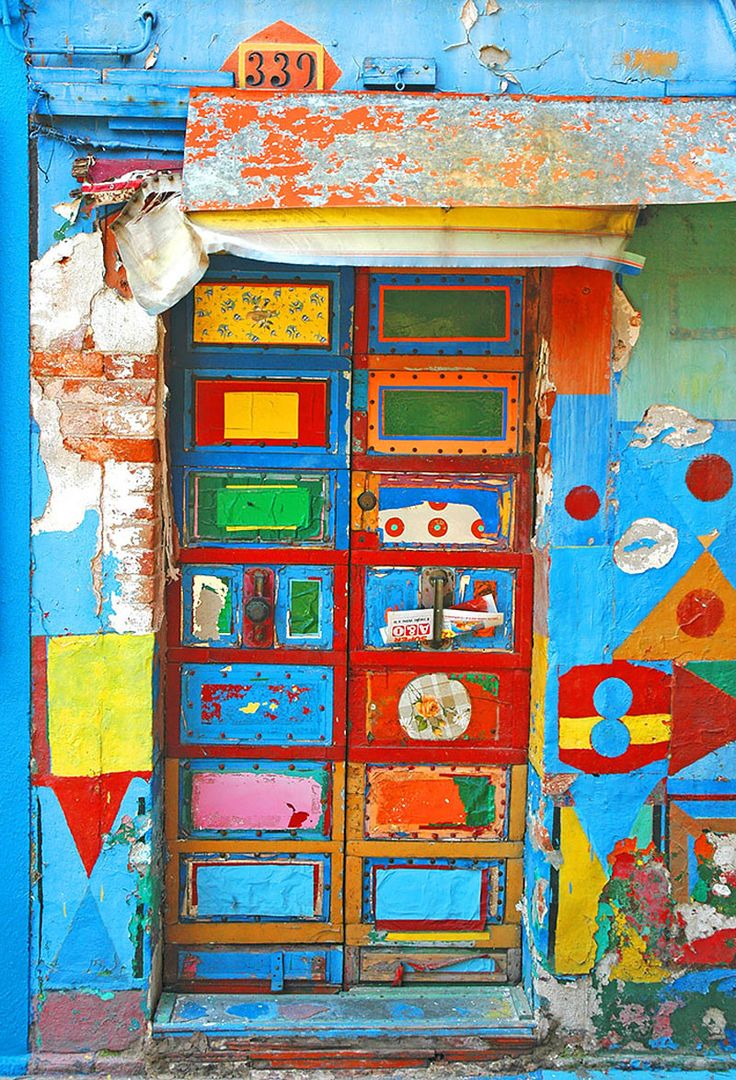 Burano,-Italy - Burano is an island of Venice that is known for wildly colorful houses. This unique front door gives away its true purpose with a newspaper tucked in the handle and an address '339' listed above.