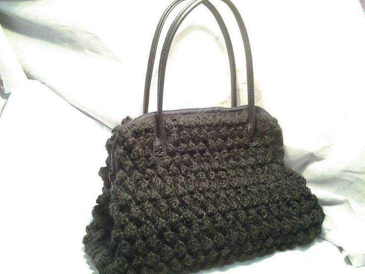 Morbida lana nera con chiusura a zip e manici in pelle.Interno tartan in lana con taschino