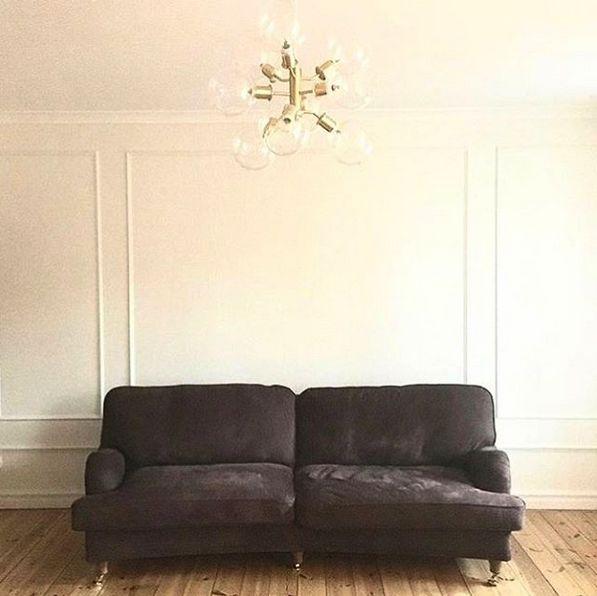 Brun Lejonet howardsoffa svängd 3-sits i skinn. Howard, soffa, mässing, hjul, sekelskift, lägenhet, vardagsrum, vägglister, väggstukatur, möbler, möbel, inredning.