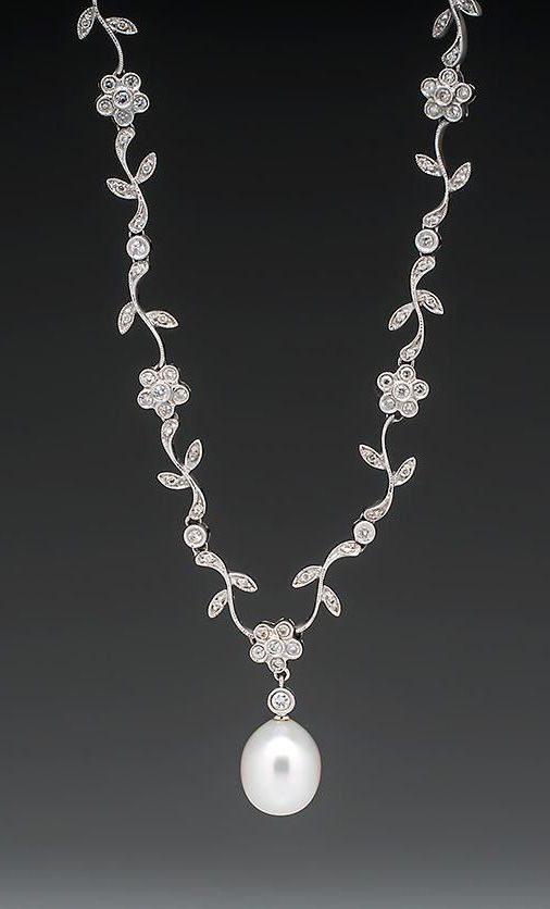This gorgeous floral motif south seas pearl necklace features a near round pearl drop that measures 12mm and weighs 9.90 carats. The chain of the necklace crafted of round brilliant diamond encrusted sections in the shapes of a flower with petals. This estate necklace is crafted of solid 18k white gold and is in very good condition.