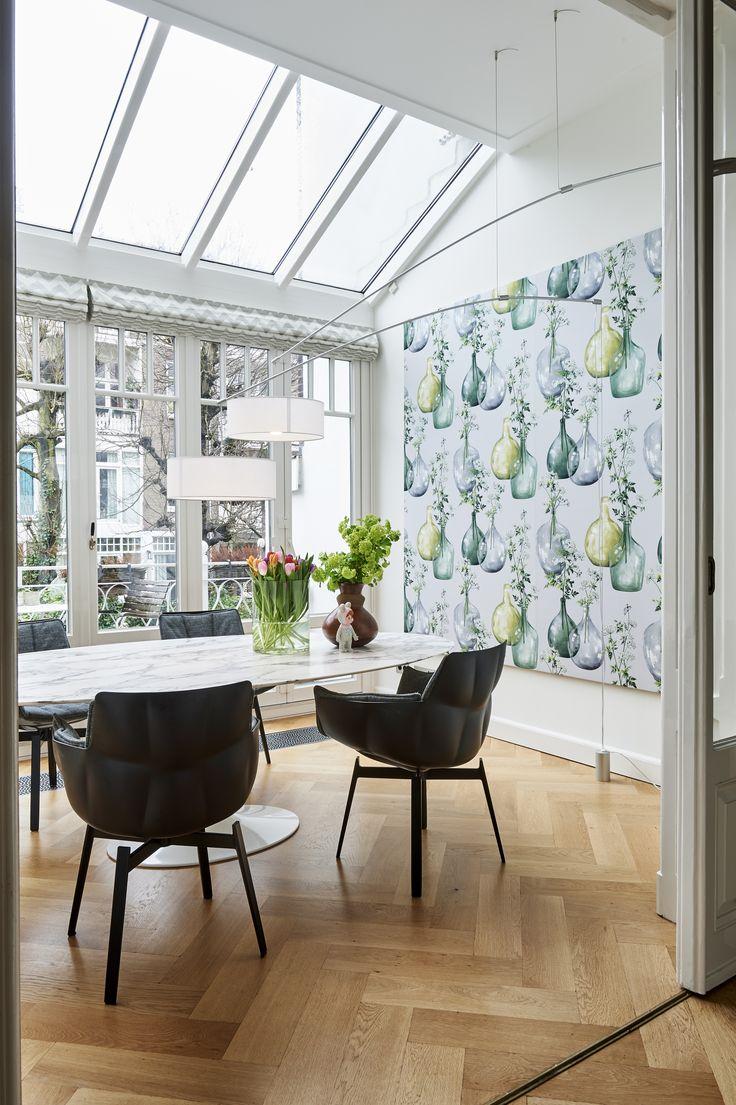 Sfeervolle eetkeuken in de serre van een monumentaal pand in Amsterdam. De combinatie van een klassieke vloer met tijdloze designer meubels zorgen voor een spectaculaire ruimte!