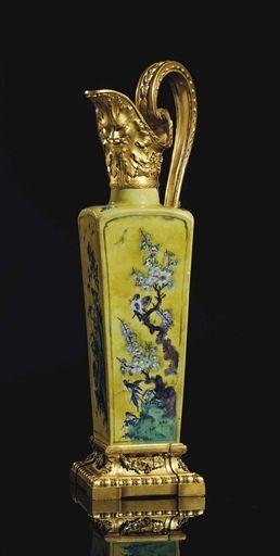 Aiguière d'époque Louis XVI, fin du 18ème siècle de la dynastie Qing Kangxi (1662-1722) Porcelaine de Chine à fond jaune rehaussé postérieument d'émaux vert et aubergine, portant la marque apocryphe de l'Empereur Chenghua (1465-1487) de la dynastie Ming sous la base, ornementation de bronze ciselé et doré, le bec décoré d'un masque et de feuilles de vigne, l'anse parcourue d'une frise, reposant sur un socle à section carrée orné de godrons