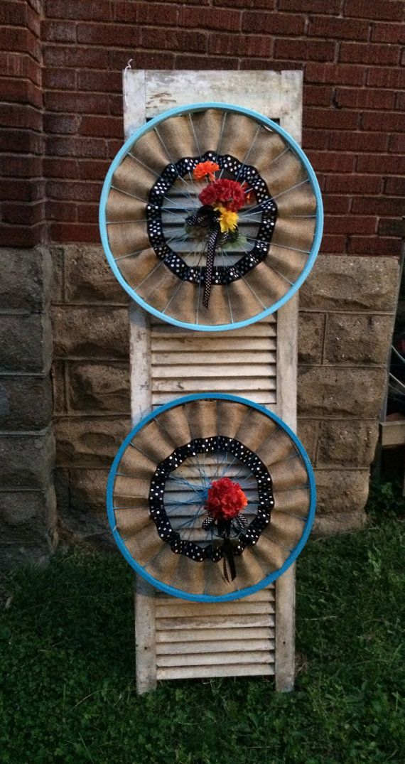 These are repurposed bicycle wheels, painted either blue or light blue, with burlap, and black & white ribbon and red and orange floral