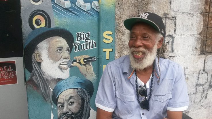 Big Youth naast zijn portret bij Small World Studios in downtown Kingston ((Jamaica)