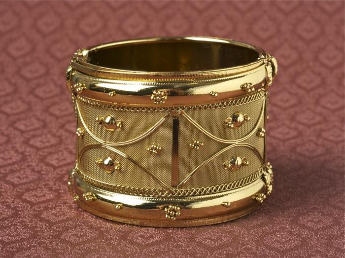 Szeroka metalowa bransoleta pięknie zdobiona złotymi elementami.