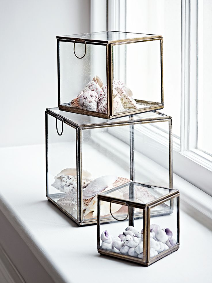 Beautifully made from quality glass with a delicate metal trim, of set of three different sized nested cubes each include a hinged lid with round handle and latch closure. Use to display your favourite jewellery, keepsakes and objet or fill with our Naked Wire Lights and watch the light bounce off the mirrored base.