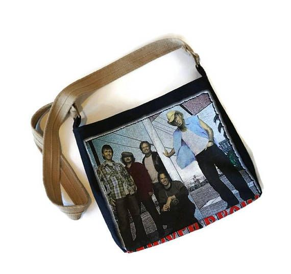 The Sawyer Brown crossbody bag is a one-of-a-kind upcycled accessory. The outside of the bag is made from a recycled black Sawyer Brown concert t-shirt featuring a graphic of the band on the front. The inside of the bag is lined in a light blue material and includes a double pocket and