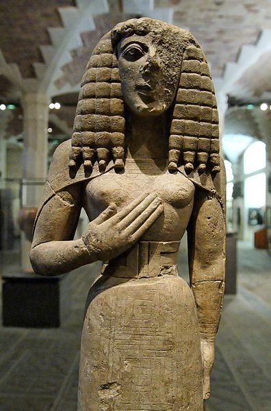 """The relatively small (75 cm high) limestone Cretan sculpture called the Lady of Auxerre, (or Kore of Auxerre), at the Louvre Museum in Paris depicts an archaic Greek goddess of c. 650 - 625 BC. It is a Kore (""""maiden""""), perhaps a votary rather than the maiden Goddess Persephone herself."""