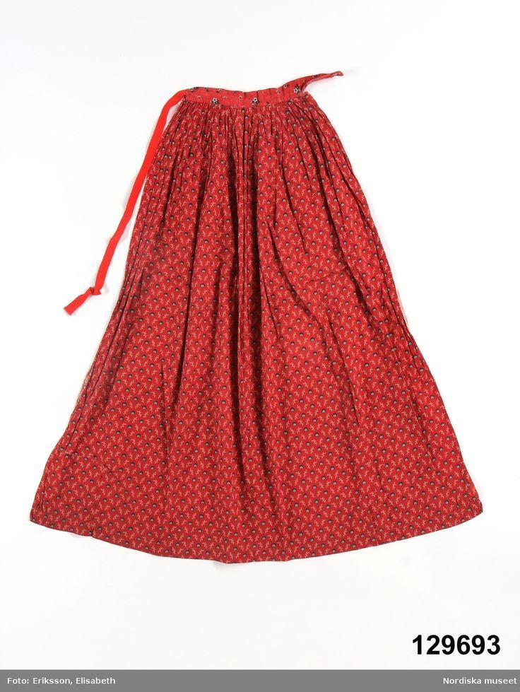 Förkläde av bomullslärft med valstryckt mönster, röd botten med små svart/vita prickar och vita kvistmönster. Små lagda veck i midjan mot linning av ett likartat bomullstryck med små blommor och prickar., i ena sidan fastsytt knytband av rött ylleband. Stadkant i båda sidor, handsydd fåll.  Anm. Mindre reva på vänster sida. Isatt lapp i högra nedre hörnet  /berit Eldvik 2012-03-29