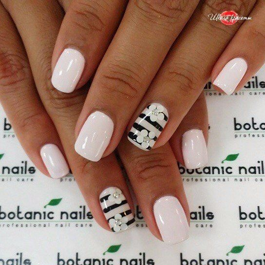 The milky white color of the background of the summer manicure is perfectly combined with a dark tan. Bright gloss of the covering effectively glitters at