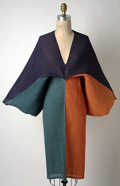 Here is an Issey Miyake dress from 1991. It comes from Japanese culture and is made of synthetic. Pleated pieces can be folded into easily stored flat objects. The 'Pleats Please' collection is featured in 2D and is displayed in recessed cutouts in the floor.