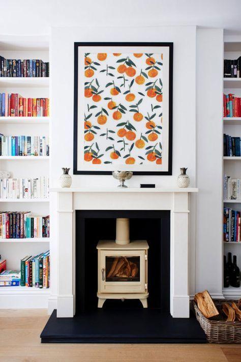 Cute fireplace, black framed print of oranges, white built-in bookshelfs // Gemütlicher Kamin mit eingebauten weißen Buchregalen und Bild voller Orangen mit schwarzem Bilderrahmen