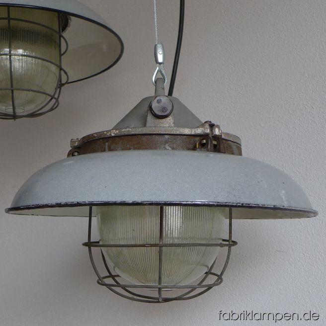 Seltene graue Bunkerlampe mit grauem Emailleschirm. Aktuell haben wir 3 Exemplare auf Lager. Die Lampen haben die Spuren der vergangenen Jarhzehnten, sie sind gereinigt und neu elektrifiziert, ausgestattet mit neuen E27 Porzellanfassungen. Material: grau (innen weiß) emailliertes Blech, gusseisernes Oberteil, Stahlgitter, Schutzglas. Höhe der Lampen 29 cm, Durchmesser Schirm 41 cm.