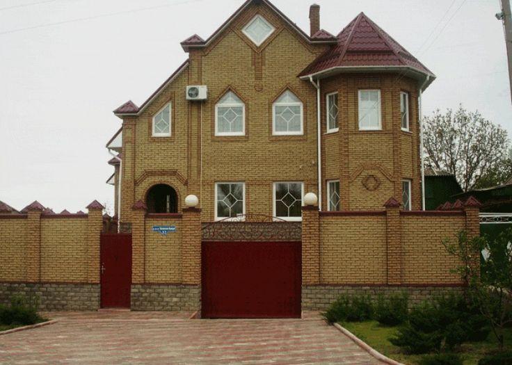 Внешняя отделка кирпичного загородного дома желтого цвета в готическом стиле с рустами