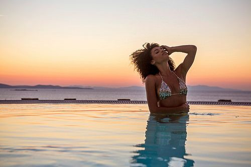 Girl enjoying the Bohemian Sea View Suite private pool, during the summer sunset at Mykonos island. You can read more information at www.bohememykonos.com/bohemian-sea-view-suite-mykonos.