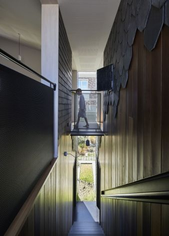The external slate cladding flows through the interior in certain areas, reinforcing the separation of different areas