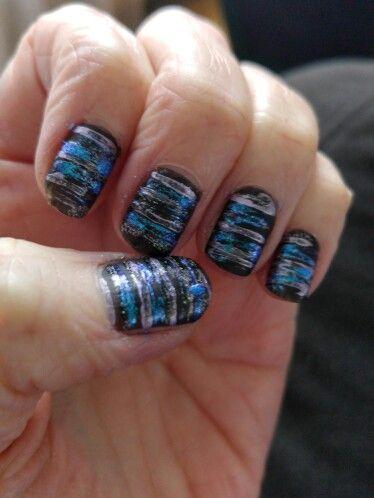 Matte zwarte nagellak. Met een flosdraad 3 kleuren in streepjes aangebracht.
