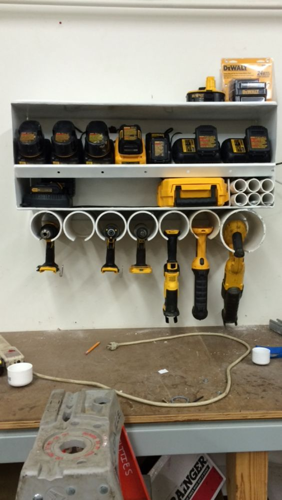 """I made this battery charger/tool shelf for our shop at work, I have a terminal strip mounted behind the charger shelf plugged in to a timer that  will run long enough to keep a charge on the batteries. I used 4"""" pvc for the drill holder and 6"""" for the sawzall holder, the 6, pieces of pipe above the saw are 1-1/2 pvc and I use those for blade storage:"""